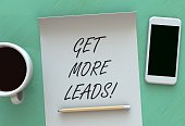 Get More Leads, message on paper, smart phone and coffee on table