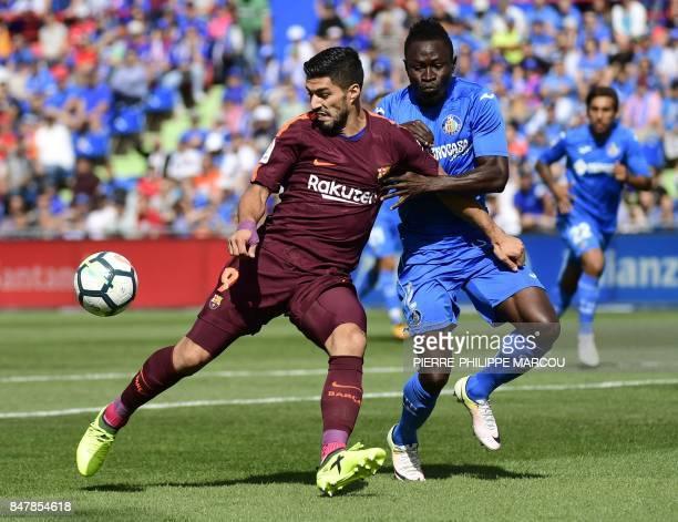 Getafe's defender from Togo Dakonam Djene vies with Barcelona's forward from Uruguay Luis Suarez during the Spanish league football match Getafe CF...