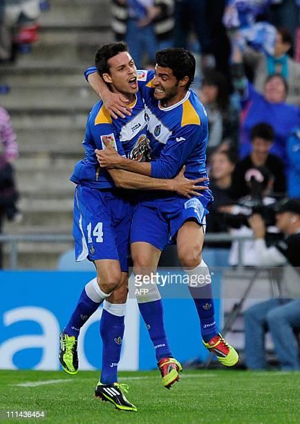 Getafe's forward Manu del Moral celebrates with teammate Getafe's defender Miguel Torres after scoring a goal against Valencia during their Liga...