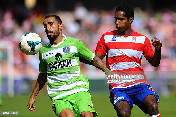 Getafe's midfielder Diego Castro vies with Granada's Colombian defender Brayan Angulo during the Spanish league football match Granada CF vs Getafe...