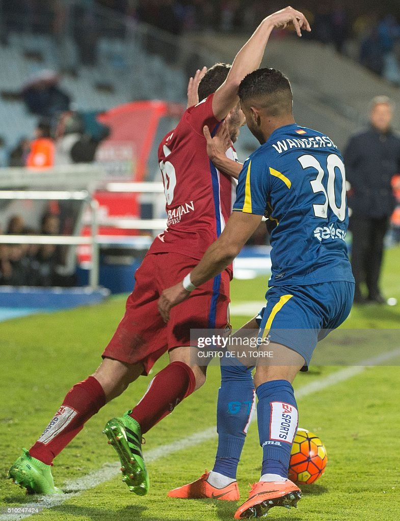 Getafe's player Wanderson (R) pushes Atletico Madrid's midfielder Koke during the Spanish league football match Getafe CF vs Club Atletico de Madrid at the Col. Alfonso Perez stadium in Getafe on February 14, 2016. TORRE