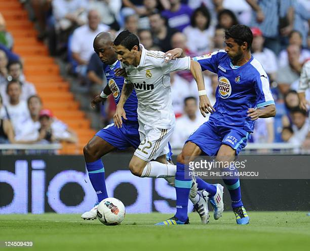 Getafe's South African defender Tshepo Masilela and Getafe's defender Miguel Torres vie with Real Madrid's Argentinian midfielder Angel di Maria...