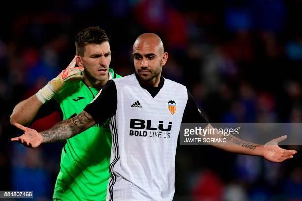 Getafe's Spanish goalkeeper Vicente Guaita reacts behind Valencia's Italian forward Simone Zaza after blocking his shot on goal during the Spanish...