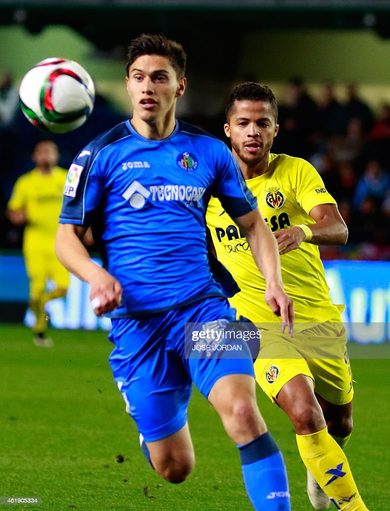 Getafe's Uruguayan defender Emiliano Velazquez (L) vies with Villarreal's Mexican forward Giovani Dos Santos during the Spanish Copa del Rey (King's Cup) round of 4 first leg football match Villarreal CF vs Getafe CF at the Madrigal stadium in Villarrreal on January 21, 2015.