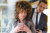 Man looking over a womans shoulder on the train at her phone screen.