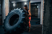 Cropped shot of a woman doing the tire flipping workout at the gym