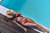 Full length top view of beautiful young woman in swimwear covering face with hat while sunbathing by the pool