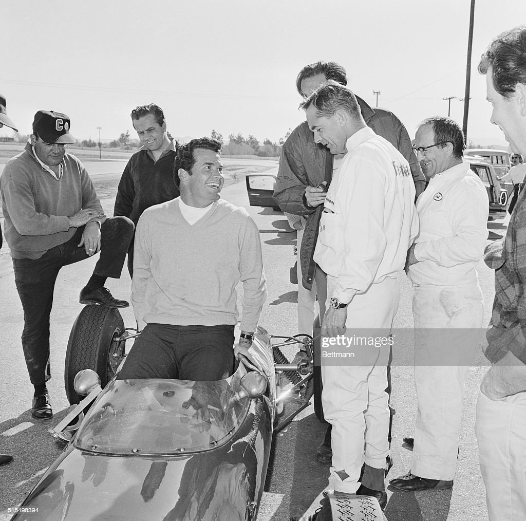 Getting in Practice Hollywood California Actor James Garner slips into a shiny racing car a Formula Junior Lotus as Phil Hill the only American...