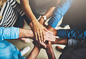 Shot of a group of creative businesspeople standing with their hands in a huddle