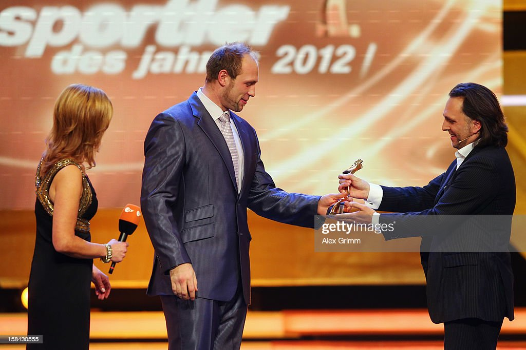 Getty Images photographer Alexander Hassenstein (R) hands over the 'Athlete of the Year 2012' trophy to <a gi-track='captionPersonalityLinkClicked' href=/galleries/search?phrase=Robert+Harting&family=editorial&specificpeople=4454412 ng-click='$event.stopPropagation()'>Robert Harting</a> during a gala at the Kurhaus Baden-Baden on December 16, 2012 in Baden-Baden, Germany.