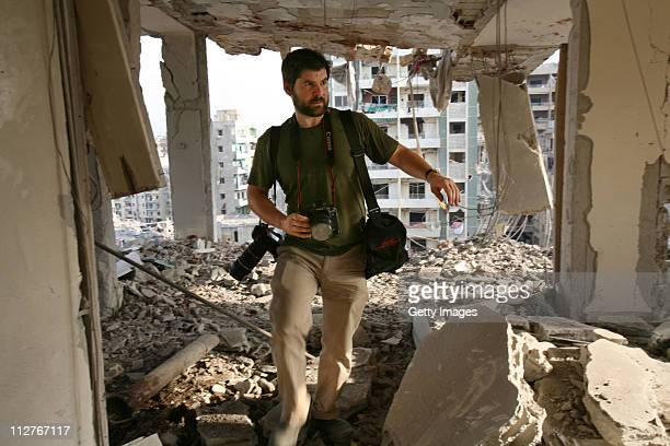 Getty Images photographer Chris Hondros walks the ruins of a building August 21 2006 in southern Beirut Lebanon Hondros who was on assignment in...