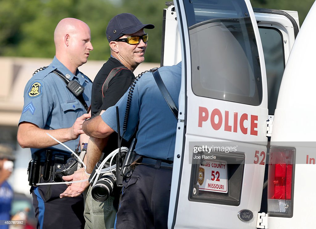 Getty Images staff photographer Scott Olson is placed into a paddy wagon after being arrested by police as he covers the demonstration following the shooting death of Michael Brown on August 18, 2014 in Ferguson, Missouri. Protesters have been vocal asking for justice in the shooting death of Michael Brown by a Ferguson police officer on August 9th.