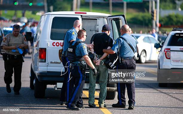 Getty Images staff photographer Scott Olson is placed into a paddy wagon after being arrested by police as the protests in the Missouri city of...