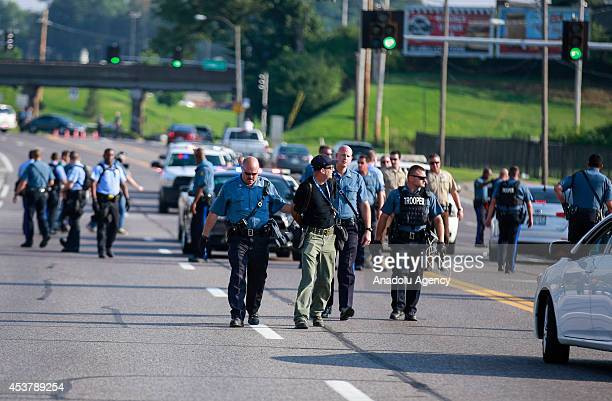 Getty Images staff photographer Scott Olson walks to paddy wagon after being arrested by police as the protests in the Missouri city of Ferguson over...