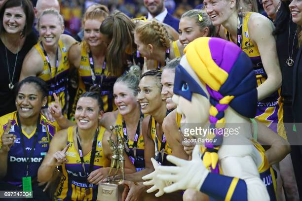 Geva Mentor and the Lightning pose for a team photo with the Suncorp Super Netball trophy after winning the Super Netball Grand Final match between...