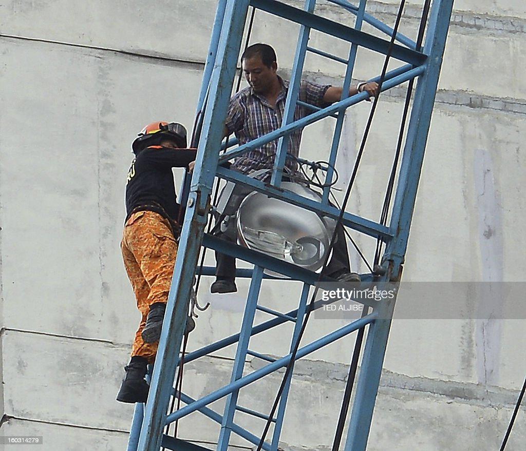 Gewan Xi (C), a Chinese national is helped by rescuers to disembark from a crane, where he climbed and allegedly attempted to jump, at a construction site in Manila on January 29, 2013, where he worked as a foreman. According to press reports, quoting police, Xi attempted to jump, after he became distraught after learning his company he was working was losing money. He was eventually rescued by firemen. AFP PHOTO/TED ALJIBE