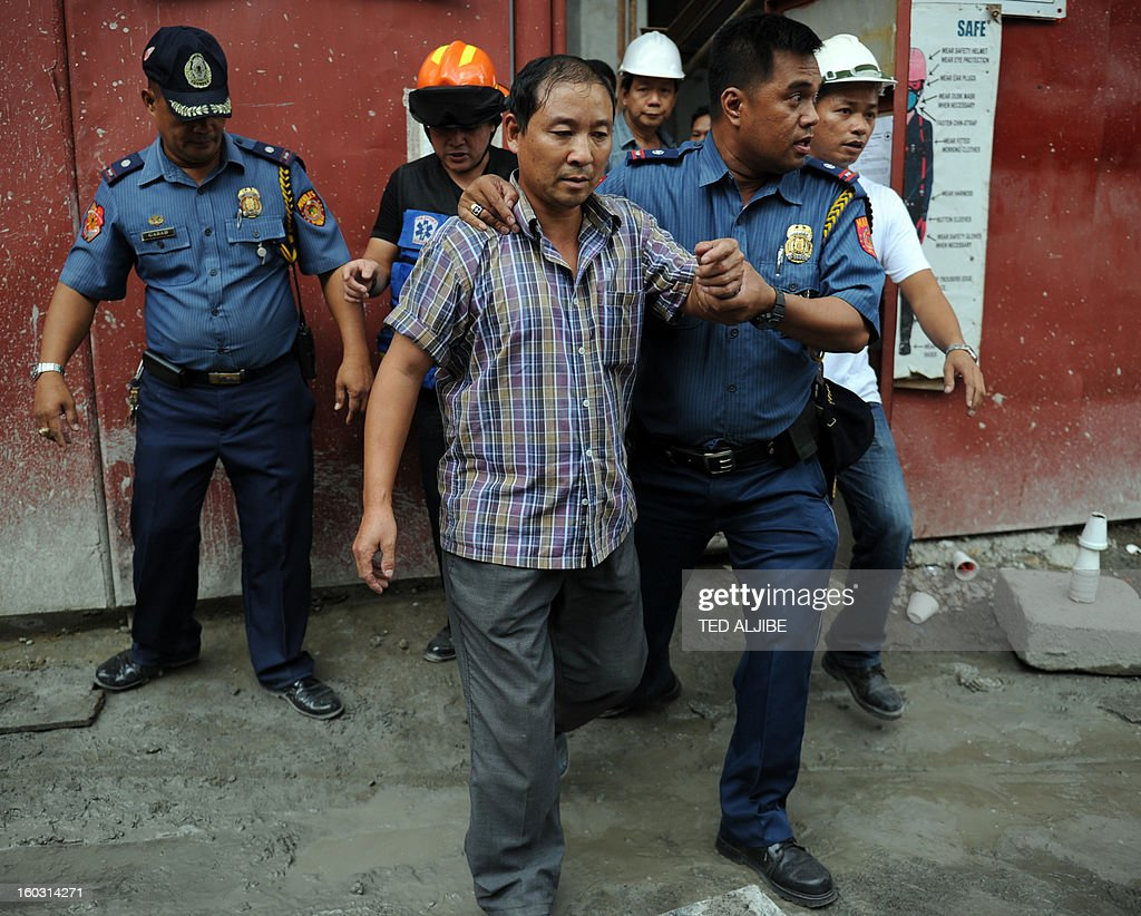 Gewan Xi (front L), a Chinese national is led away by police after rescuers helped him disembark from a crane, where he climbed and allegedly attempted to jump at a construction site in Manila on January 29, 2013, where he worked as a foreman. According to press reports, quoting police, Xi attempted to jump, after he became distraught after learning his company he was working was losing money. He was eventually rescued by firemen.