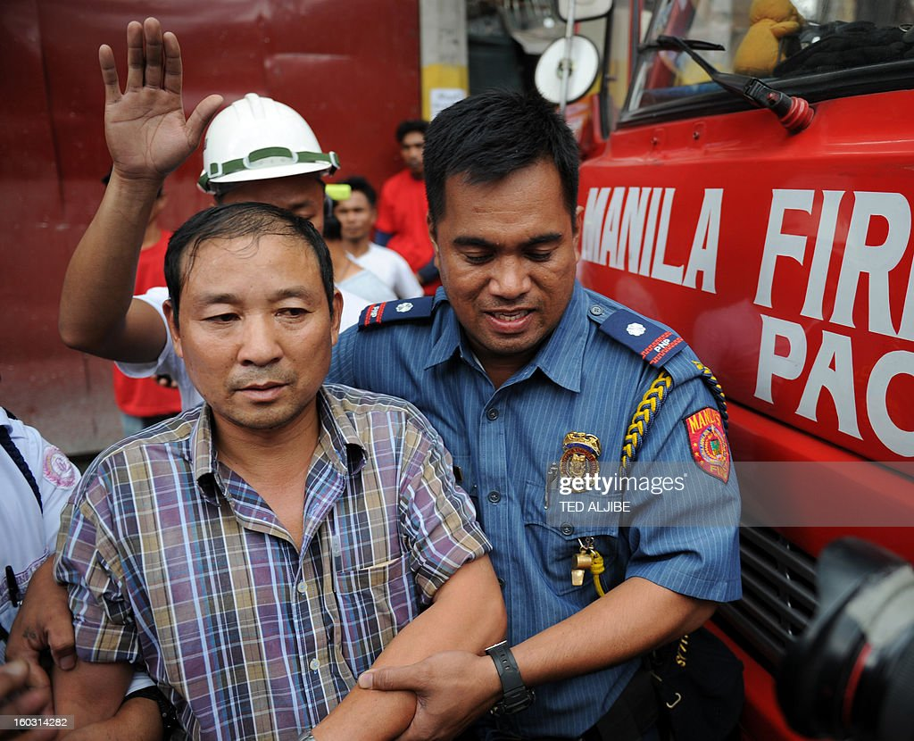 Gewan Xi (front L), a Chinese national is led away by police after rescuers helped him disembark from a crane, where he climbed and allegedly attempted to jump at a construction site in Manila on January 29, 2013, where he worked as a foreman. According to press reports, quoting police, Xi attempted to jump, after he became distraught after learning his company he was working was losing money. He was eventually rescued by firemen. AFP PHOTO/TED ALJIBE