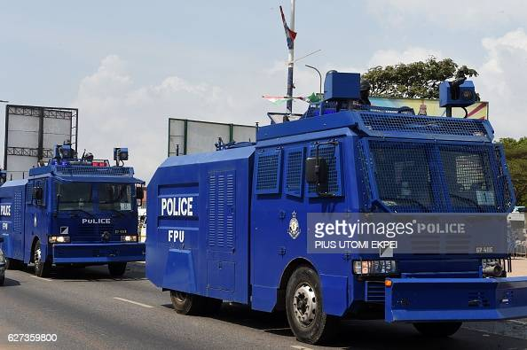 A Ghanaian Police Force water cannon followed by other police vehicles parade along a street in Accra on December 3 2016 in a show of force ahead of...
