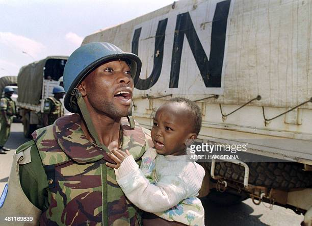 A Ghanaian United Nations soldier evacuates 13 June 1994 a Tutsi child from a governmentheld sector of Kigali to Kabouga in Kigali's outskirts Up to...