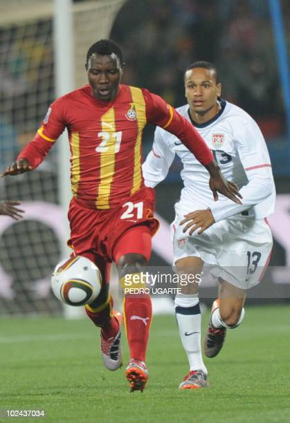 Ghana's midfielder Kwadwo Asamoah is challenged for the ball by US midfielder Ricardo Clark during the 2010 World Cup round of 16 football match USA...