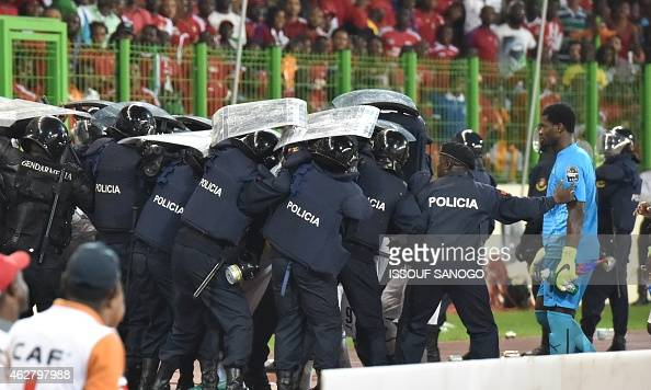 Ghana's national football team players leave the pitch protected by riot police at the halftime of the 2015 African Cup of Nations semifinal football...
