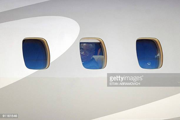 Ghana's President Jhon Atta Mills peers from the porthole of the plane upon arrival in Margarita Island Nueva Esparta state northwestern Venezuela on...
