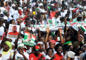 Ghana's ruling National Democratic Congress supporters carry pictures of reelected Ghanaian President John Dramani Mahama as they gather at Kwame...