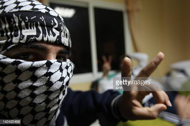 Ghassan his face covered with the trademark chequerred keffiyeh and a headband that reads in Arabic 'There is no God but God Mohammed is his...
