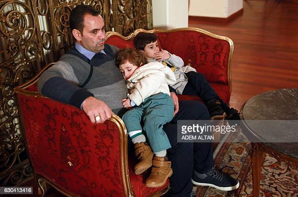 Ghassan the father of the Syrian girl Bana alAbed known as Aleppo's tweeting girl holds his sons Nour and Laith during an interview in Ankara Turkey...