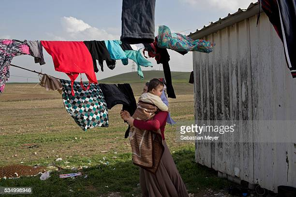 Ghazal hangs up the family laundry while holding her grandson Mazal The family of Yezidis displaced from Sinjar live next to an oil refinery in the...