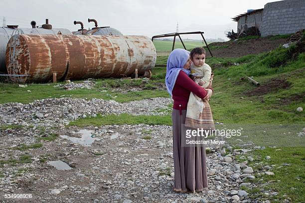 Ghazal holds her grandson Mazal a few feet from where they live in a shipping container The family of Yezidis displaced from Sinjar live next to an...