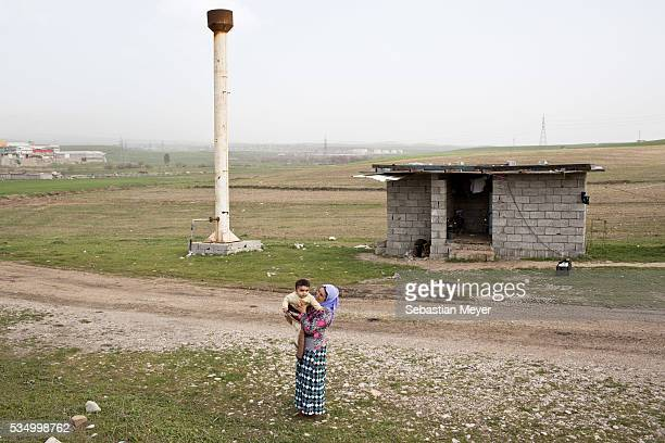 Ghazal holds her grandson Mazal in front of the building the family use as a toilet shower and sink Ghazal a Yezidi woman from Sinjar lives with her...