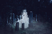Ghost girl walking on cemetery. Halloween theme.
