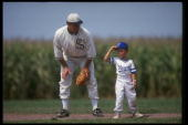 A 'ghost player' recreating the role of Chicago White Sox legend Shoeless Joe Jackson plays ball with a young tourist at the baseball field created...