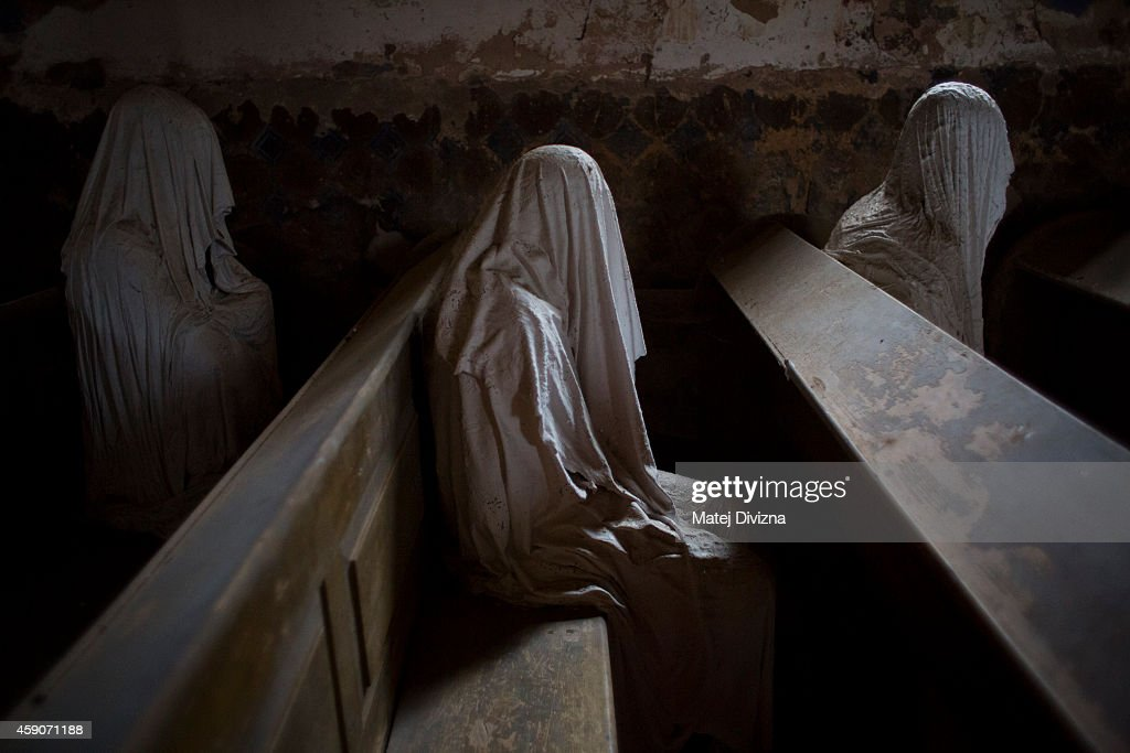 Ghost statues by artist Jakub Hadrava are placed at the St. George's church near Plzen on November 16, 2014 in Lukova, Czech Republic. Artist Jakub Hadrava created 32 plaster life-size ghost statues, which symbolize Sudeten Germans who lived in the village. St. George's church, which was build in the north-western Bohemian region of the Czech Republic in 1352, fell into disrepair after the roof collapsed during a funeral service in 1968. Hadrava's aim is to make the church more attractive for visitors and to gain money for renovation work. According to voluntary church manager Petr Koukl, about 2500 people from around the world have been visiting the church this year.