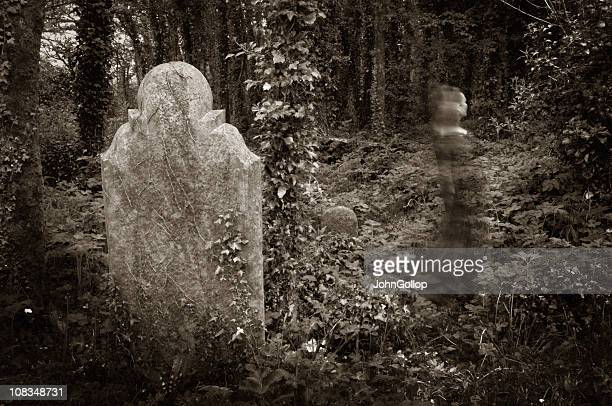 Ghostly image in front of a gravestone in a graveyard