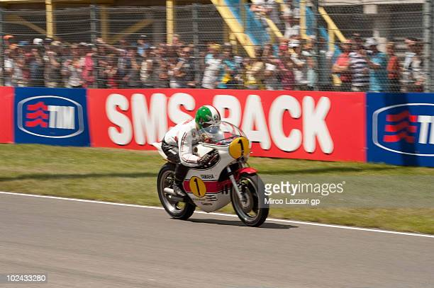 Giacomo Agostini of Italy heads down a straight with his old Yamaha bike before the MotoGP race of Grand Prix of Netherlands in TT Assen Circuit on...