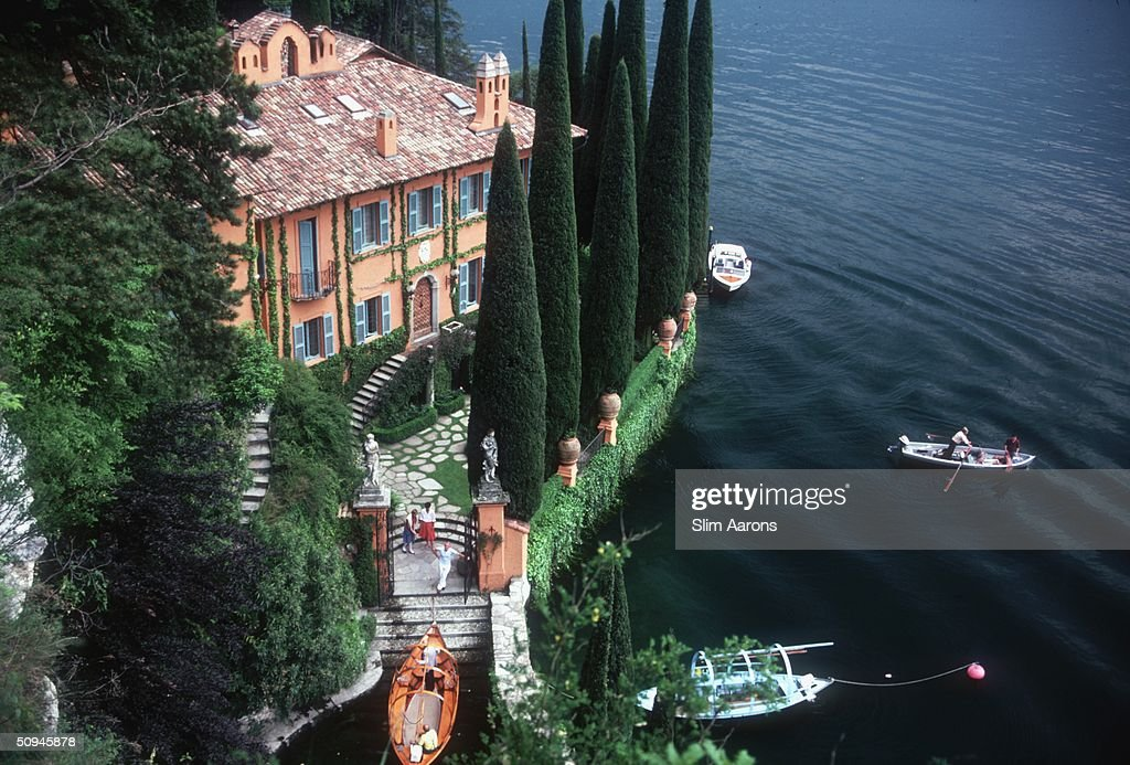Giacomo and Stefania Montegazza welcome guests arriving by boat at their villa, La Casinella, on Lake Como, 1983.