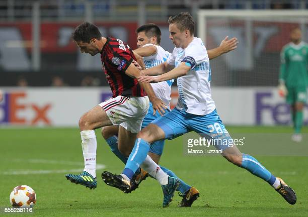 Giacomo Bonaventura of AC Milan is challenged by Filip Bradaric of HNK Rijeka during the UEFA Europa League group D match between AC Milan and HNK...