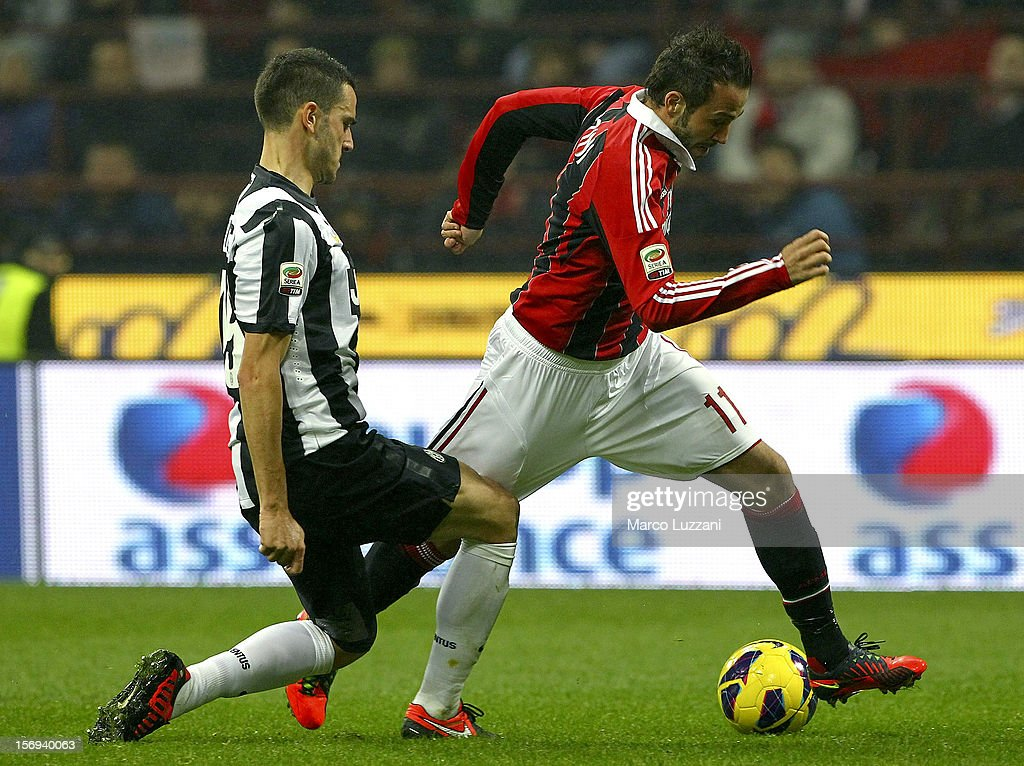 Giampaolo Pazzini (R) of AC Milan competes for the ball with Leonardo Bonucci (L) of Juventus FC during the Serie A match between AC Milan and Juventus FC at San Siro Stadium on November 25, 2012 in Milan, Italy.
