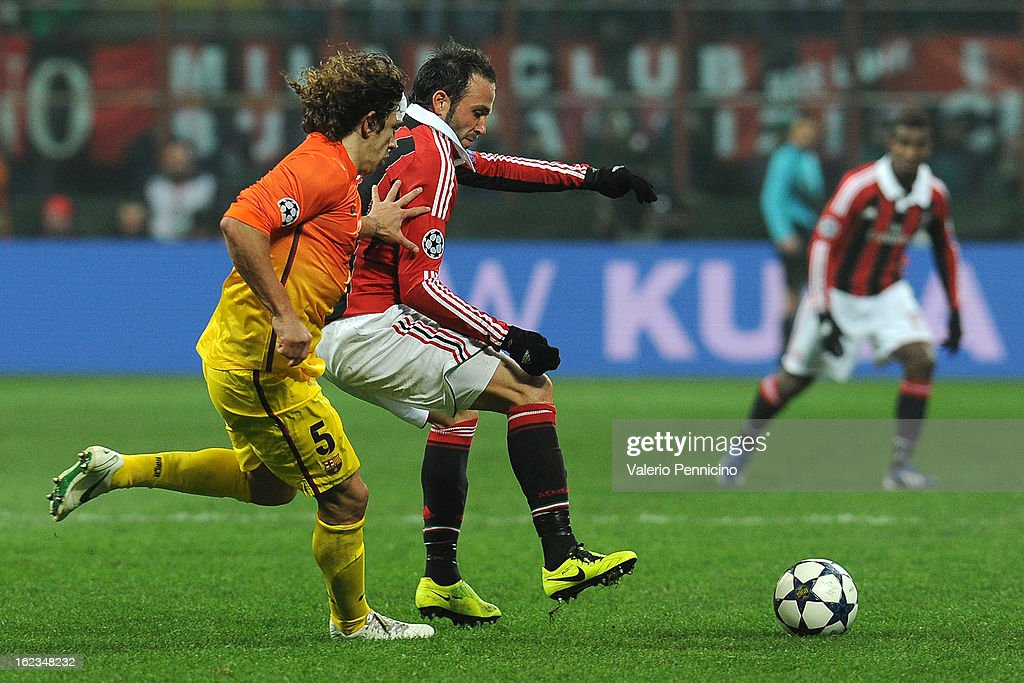 Giampaolo Pazzini (R) of AC Milan is challenged by Carles Puyol of Barcelona during the UEFA Champions League Round of 16 first leg match between AC Milan and Barcelona at San Siro Stadium on February 20, 2013 in Milan, Italy.