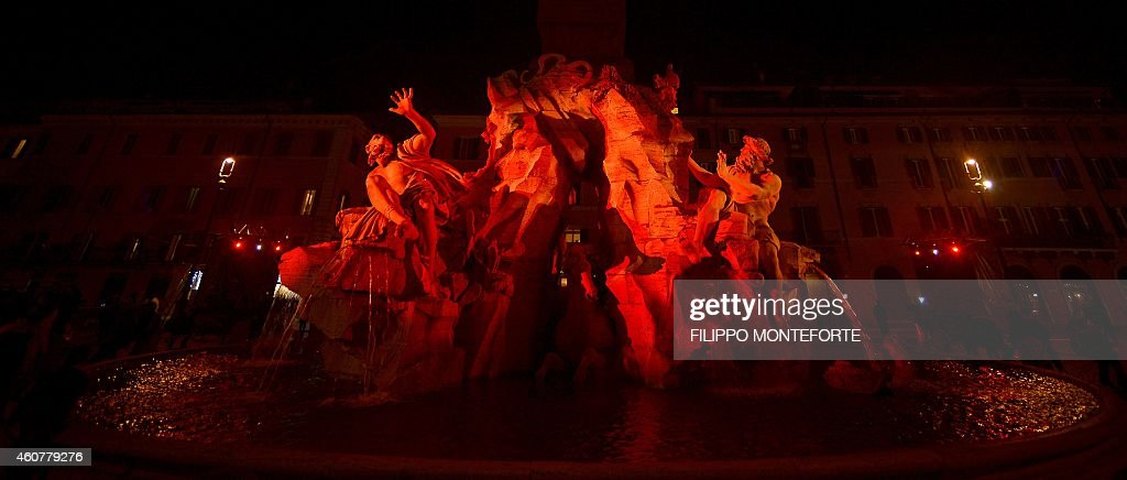 Gian Lorenzo Bernini's Fountain of the Four Rivers is iluminated in red for the traditional Christmas decorations in Rome's Piazza Navona on December 22, 2014.