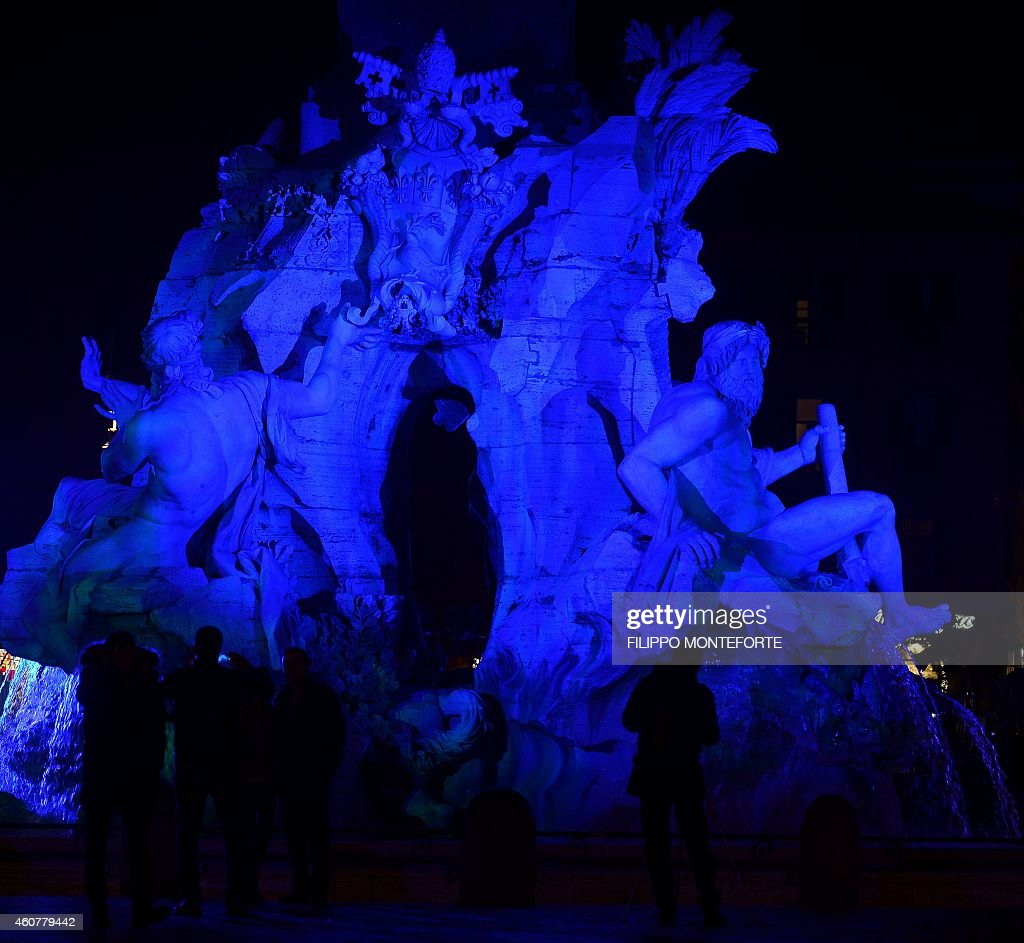Gian Lorenzo Bernini's Fountain of the Four Rivers is iluminated in blue light for the traditional Christmas decorations in Rome's Piazza Navona on December 22, 2014. AFP PHOTO / FILIPPO MONTEFORTE
