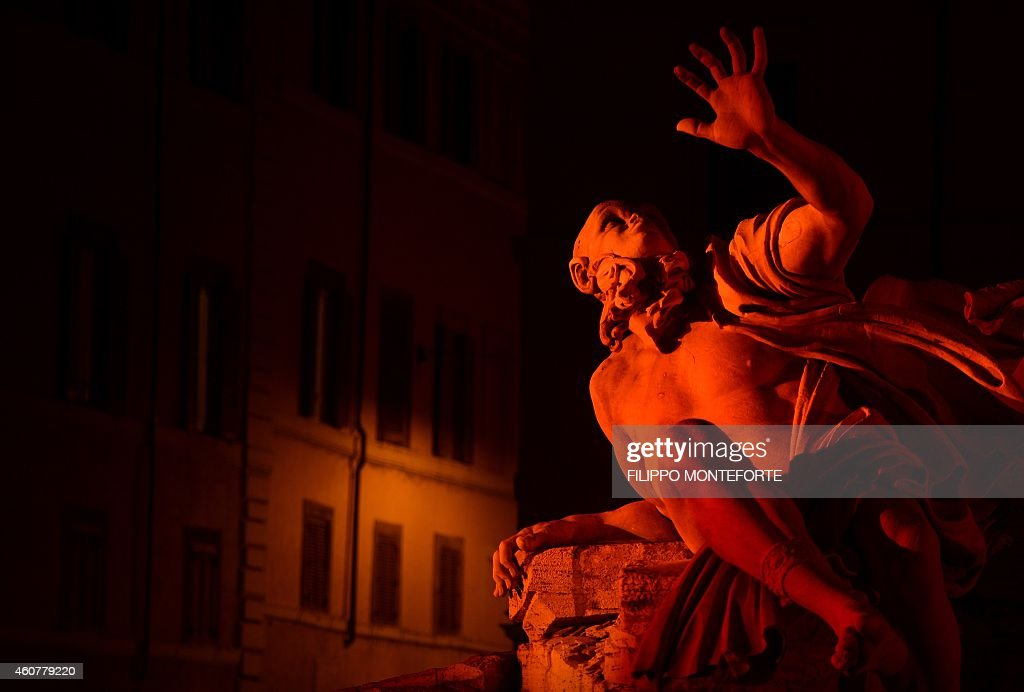 Gian Lorenzo Bernini's Fountain of the Four Rivers is lit in red for the traditional Christmas decorations in Rome's Piazza Navona on December 22, 2014 AFP PHOTO / FILIPPO MONTEFORTE