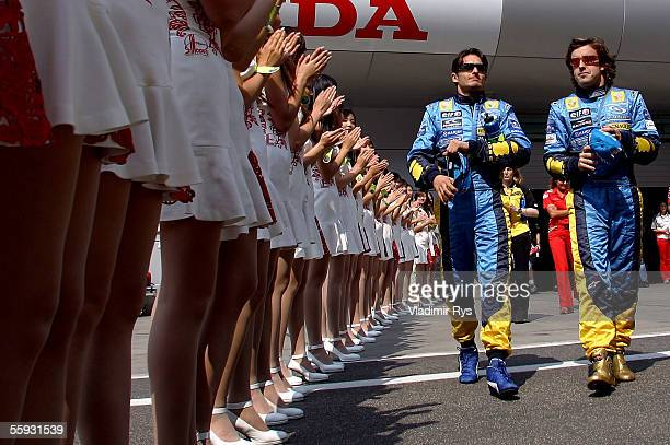 Giancarlo Fisichella of Italy and his team mate and World Champion Fernando Alonso of Spain and Renault walk on the pit lane to attend the driver's...