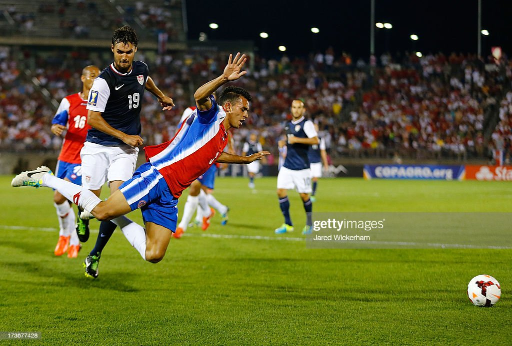 Giancarlo Gonzalez #3 of Costa Rica falls to the ground in front of <a gi-track='captionPersonalityLinkClicked' href=/galleries/search?phrase=Chris+Wondolowski&family=editorial&specificpeople=2579265 ng-click='$event.stopPropagation()'>Chris Wondolowski</a> #19 of the United States in the second half during the CONCACAF Gold Cup match at Rentschler Field on July 16, 2013 in East Hartford, Connecticut.