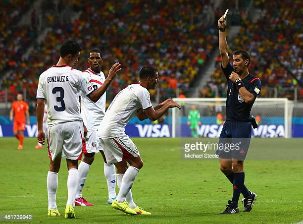 Giancarlo Gonzalez of Costa Rica is shown a yellow card by referee Ravshan Irmatov as Michael Umana gestures during the 2014 FIFA World Cup Brazil...