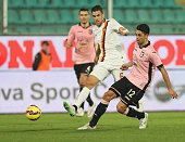 Giancarlo Gonzalez of Palermo competes for the ball with Kevin Strootman of Roma during the Serie A match between US Citta di Palermo and AS Roma at...