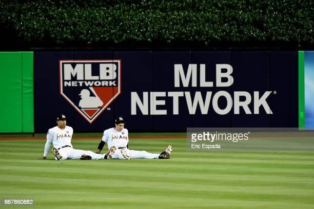 Giancarlo Stanton and Christian Yelich of the Miami Marlins sit in the outfield during a power outage in the 4th inning of the game against the...